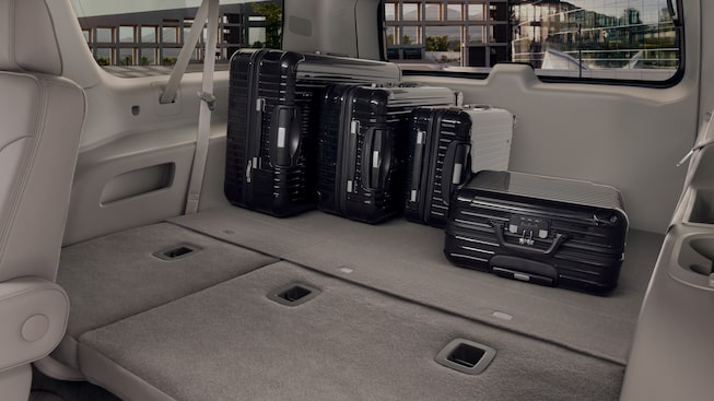 Interior view showing the flat seats of the Yukon Denali with luggage.
