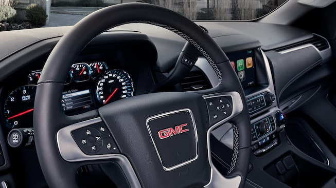 2019 GMC Yukon SLT's leather-wrapped steering wheel.