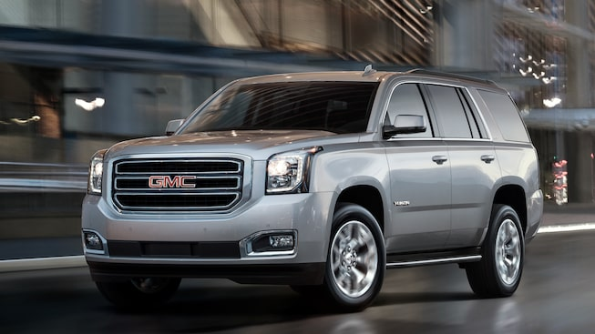 The GMC Yukon SUV in Quicksilver Metallic driving along the city streets.