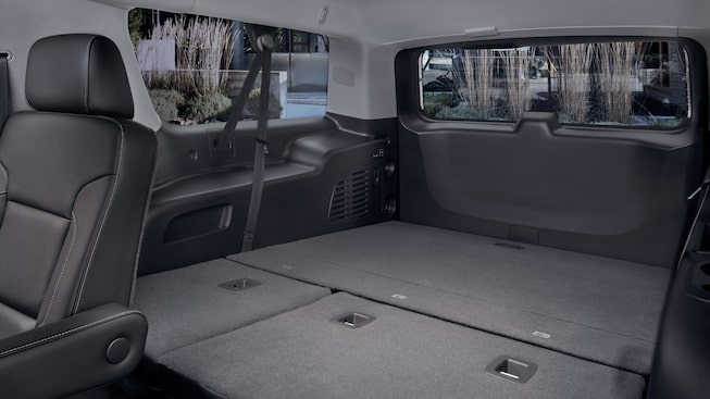 Convenience features of the 2019 Yukon 8-seater SUV in Jet Black interior, showing spacious cargo room with folded second and third row passenger seats.