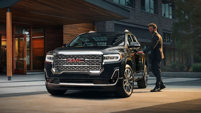 A Man Opening The Door Of The 2020 GMC Acadia Denali Luxury SUV.