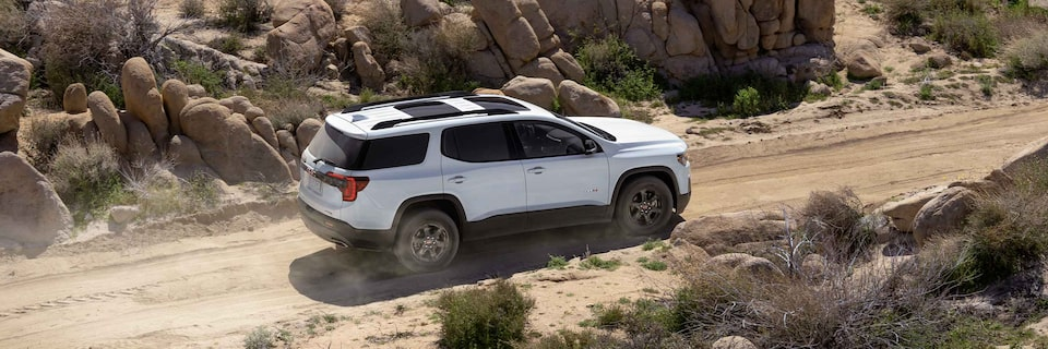 Side view of a 2021 GMC Acadia AT4 driving off-road.