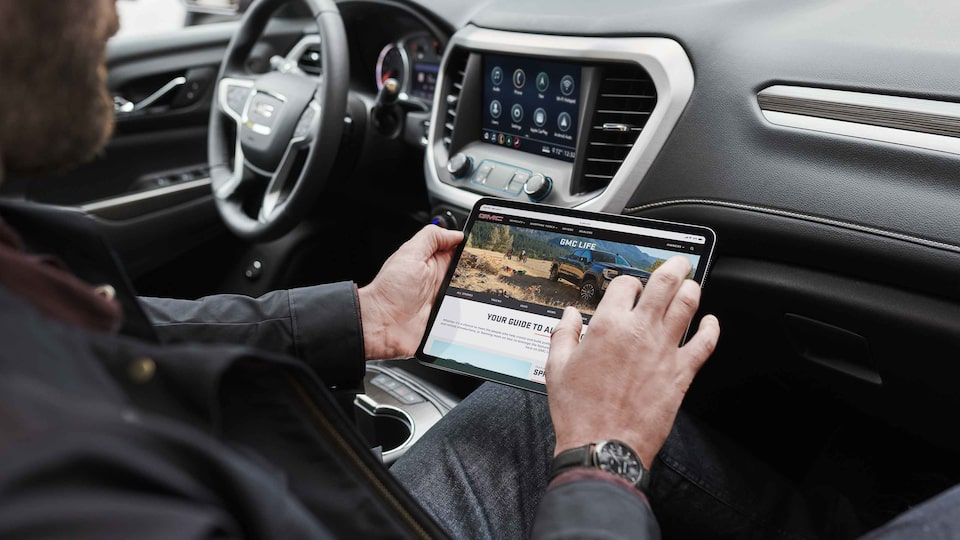 Man using a tablet in a 2021 GMC Acadia.