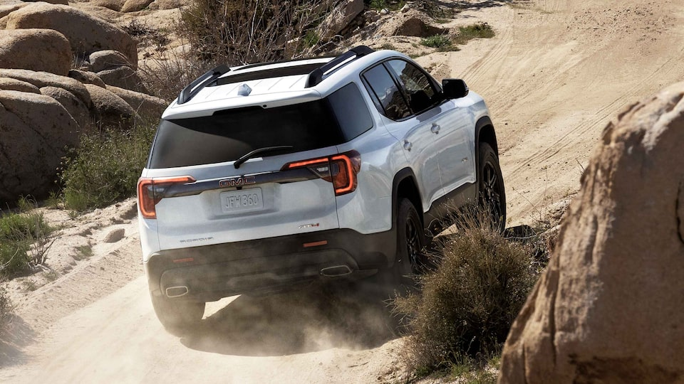 Rear view of a 2021 GMC Acadia AT4 driving off-road.