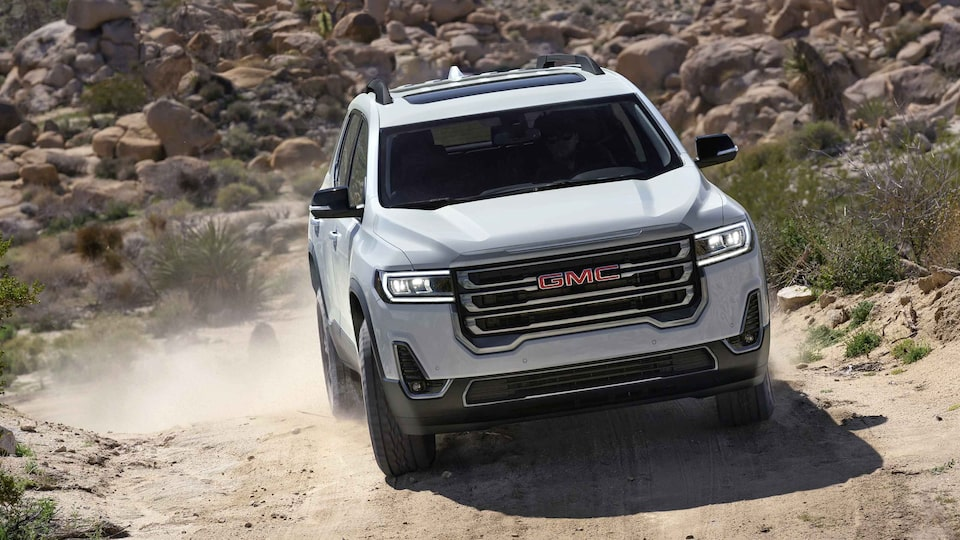 Front view of a 2021 GMC Acadia AT4 driving off-road.
