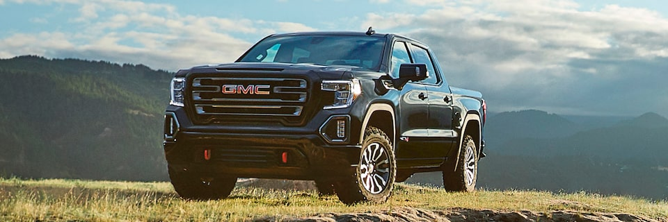 2020 GMC Sierra AT4 Off Road Truck In Front Of A Mountain Background.