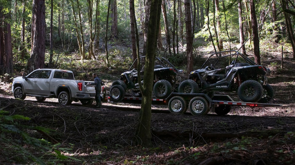 2020 Sierra Heavy Duty Pickup Truck: Towing Two ATVs In The Woods.