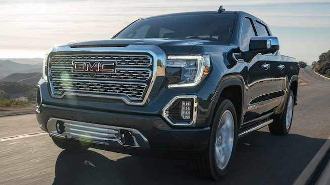 Front side view of the 2021 Sierra 1500 Denali driving on the road.