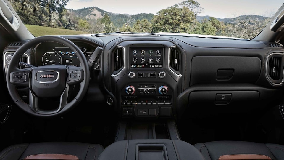 2021 Sierra HD AT4 athletic interior dashboard featuring the steering wheel and infotainment system.