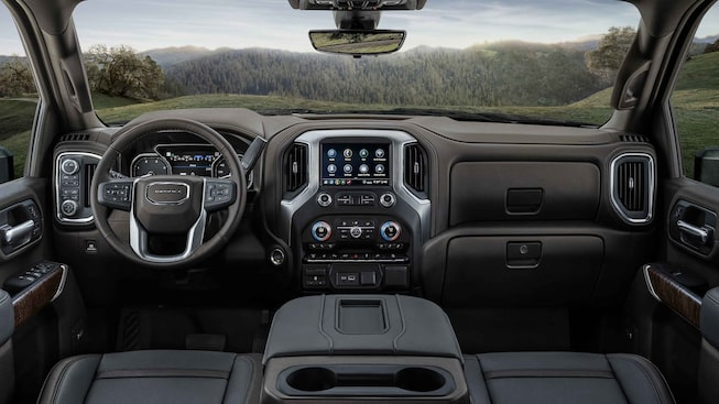 2021 GMC Sierra HD Denali front interior featuring the dashboard, steering wheel, and infotainment system.