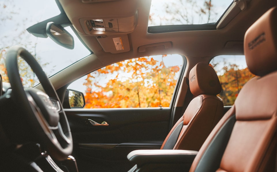 Interior of the 2019 GMC Acadia featuring brown leather seats and a wide sunroof.